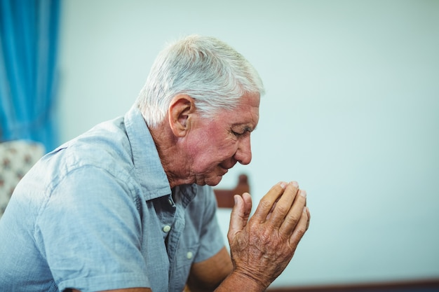 Bezorgd senior man zit in de woonkamer Premium Foto