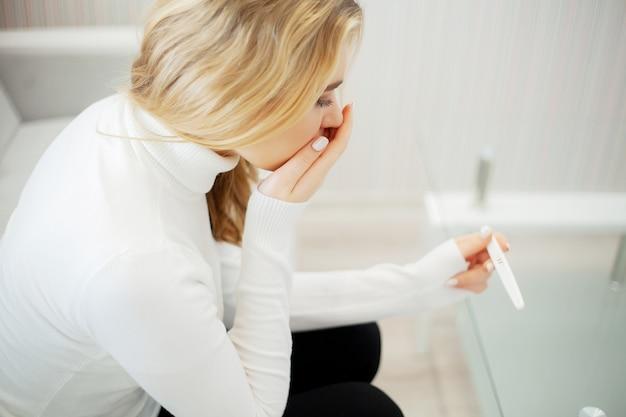 Bezorgd trieste vrouw kijken naar een zwangerschapstest na het resultaat Premium Foto