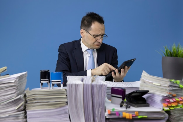 Bezorgd zakenman rekent op calculator zittend aan tafel met stapels papieren in kantoor Premium Foto