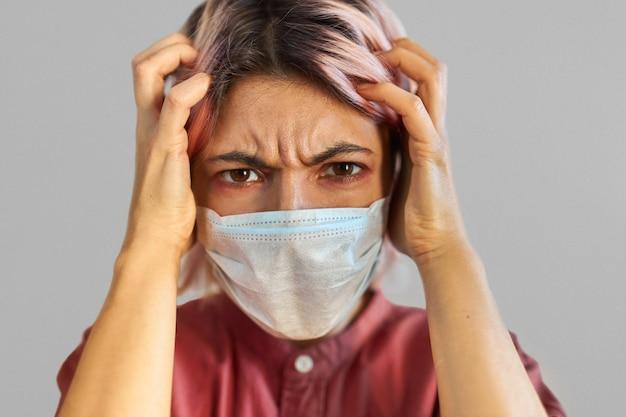 Bezorgde jonge vrouw in paniek die lijdt aan ernstige hoofdpijn, met covid-19-symptomen. benadrukt meisje in medisch gezichtsmasker bezorgd over besmettelijke luchtweginfectie of seizoensgriep Gratis Foto