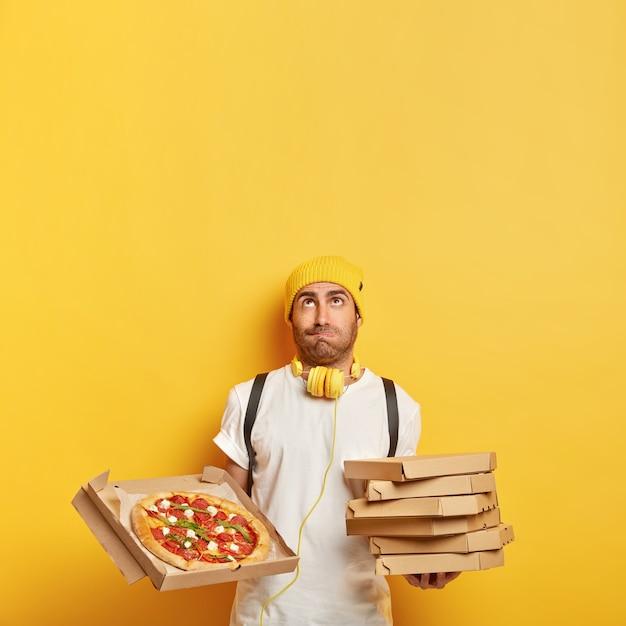 Bezorger brengt kartonnen pizzadozen voor klant, kijkt naar boven, draagt gele hoed, wit t-shirt, transporteert fastfood, geïsoleerd op gele muur, kopie ruimte voor uw promotie Gratis Foto