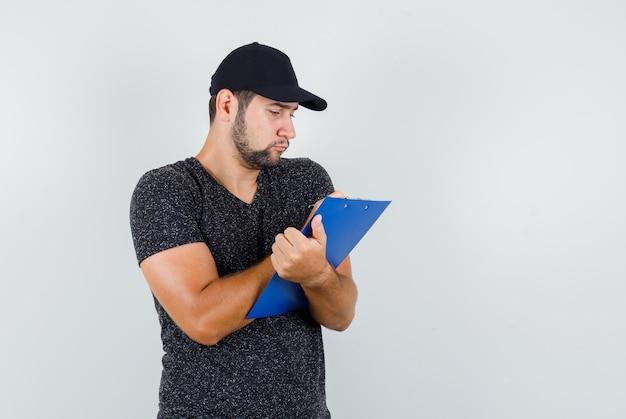 Bezorger die aantekeningen maakt op klembord in t-shirt en pet en bezig kijkt Gratis Foto
