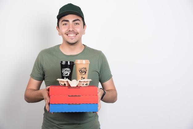 Bezorger die drie dozen pizza en koffie op witte achtergrond houdt. Gratis Foto