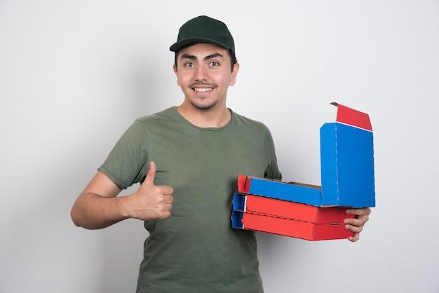 Bezorger duimen opdagen en pizzadozen uitvoering op witte achtergrond. Gratis Foto