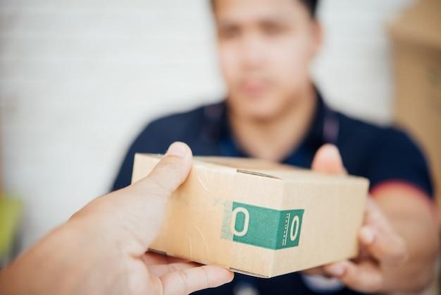 Bezorger glimlacht en houdt een kartonnen doos Gratis Foto