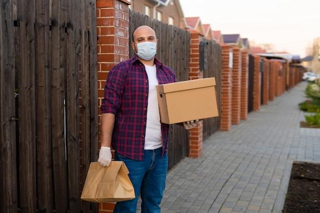 Bezorger houdt een kartonnen doos en draagt een gezichtsmasker voor coronaviruspreventie Premium Foto