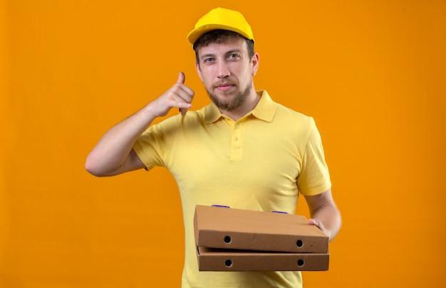 Bezorger in geel poloshirt en pet met pizzadozen bel me gebaar kijken zelfverzekerd glimlachend vriendelijk staande op oranje Gratis Foto