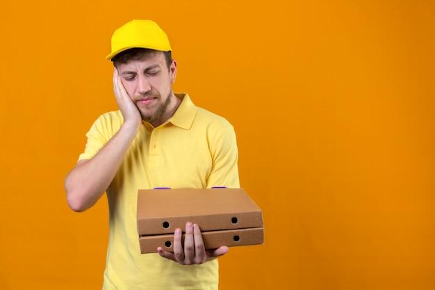 Bezorger in geel poloshirt en pet met pizzadozen die er slecht uitzien staan met de hand op de wang die lijden aan kiespijn op oranje Gratis Foto