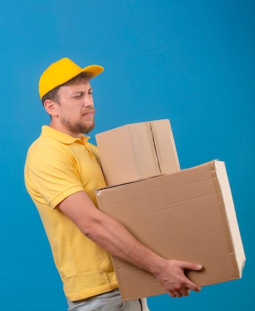 Bezorger in geel poloshirt en pet staat met grote kartonnen dozen die lijden aan zwaar gewicht op blauw Gratis Foto