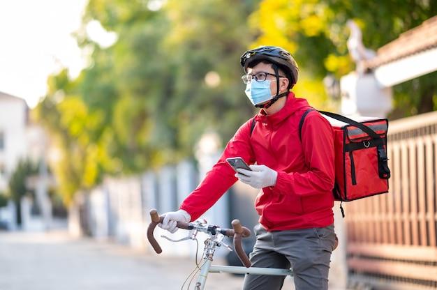 Bezorger met beschermend masker om het coronavirus te vermijden kijk naar de telefoon om het adres van de klant te vinden via de applicatie. Premium Foto