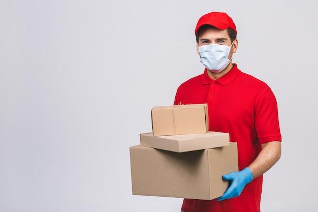 Bezorger werknemer in rode dop lege t-shirt uniforme gezichtsmasker handschoenen houden lege kartonnen doos Premium Foto
