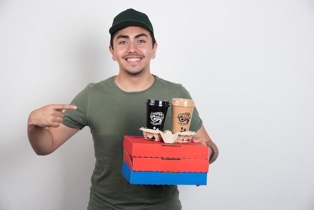 Bezorger wijzend op drie dozen pizza en koffie op witte achtergrond. Gratis Foto