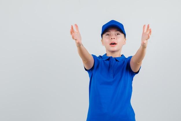 Bezorgvrouw in blauw t-shirt en pet die armen strekt alsof ze iets ontvangen Gratis Foto