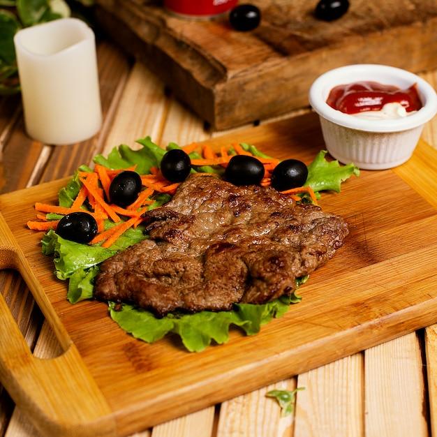 Biefstuk dun geserveerd met ketchupmayonaise en groentesalade. Gratis Foto
