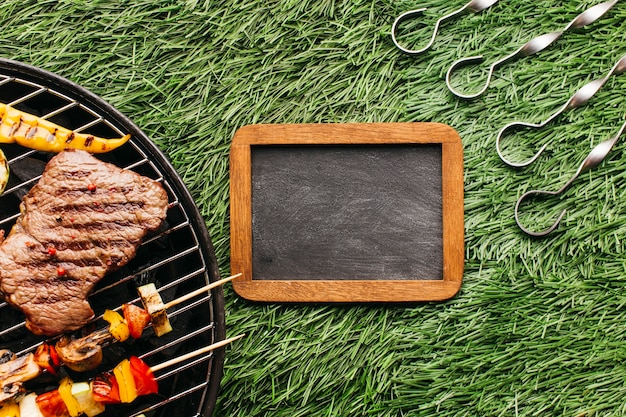 Biefstuk en worsten die op barbecuekieuwel dichtbij lege lei en metaalvleespen over grasmat roosteren Gratis Foto