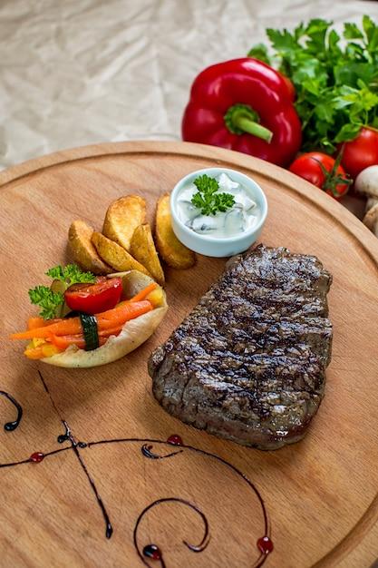 Biefstuk geserveerd met friet en gekookte groenten in houten schotel Gratis Foto