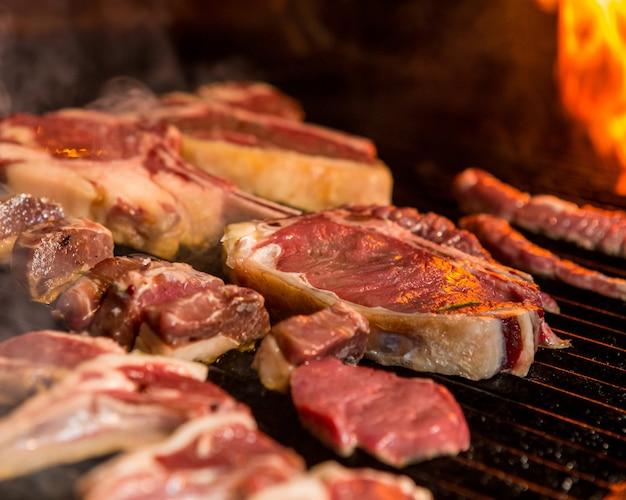 Biefstuk koken op een grill naast de vlam Gratis Foto