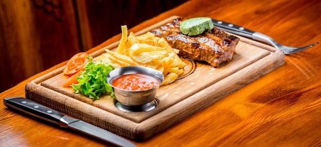 Biefstuk met pepersaus en gegrilde groenten op snijplank Premium Foto