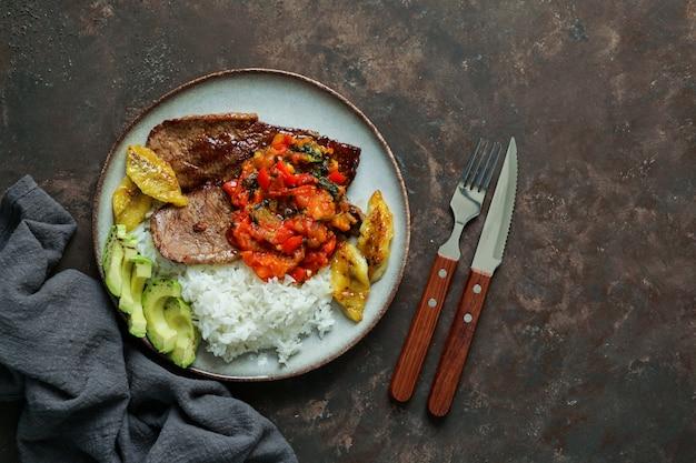 Biefstuk met tomatensaus, rijst, avocado, bananen friet Premium Foto
