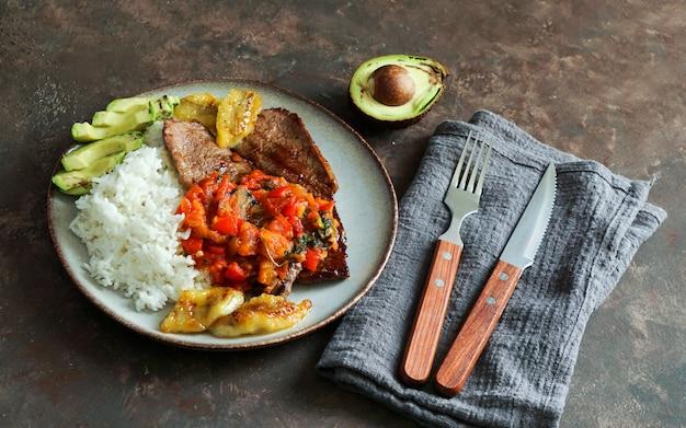 Biefstuk met tomatensaus, rijst, avocado en friet van bananen Premium Foto
