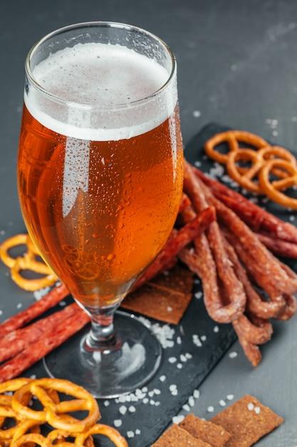 Bier en smakelijk bier snacks set. tafel met mok bier, houten bord met worst Premium Foto