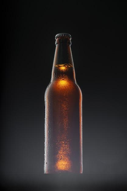 Bierfles op donkere achtergrond, exemplaarruimte Premium Foto