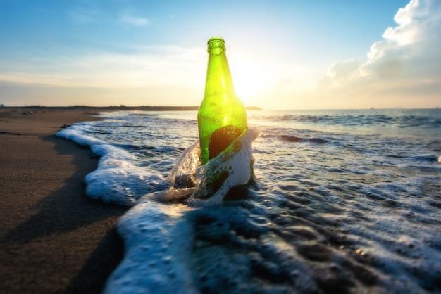 Bierfles op een zandstrand met heldere hemel en golf Premium Foto