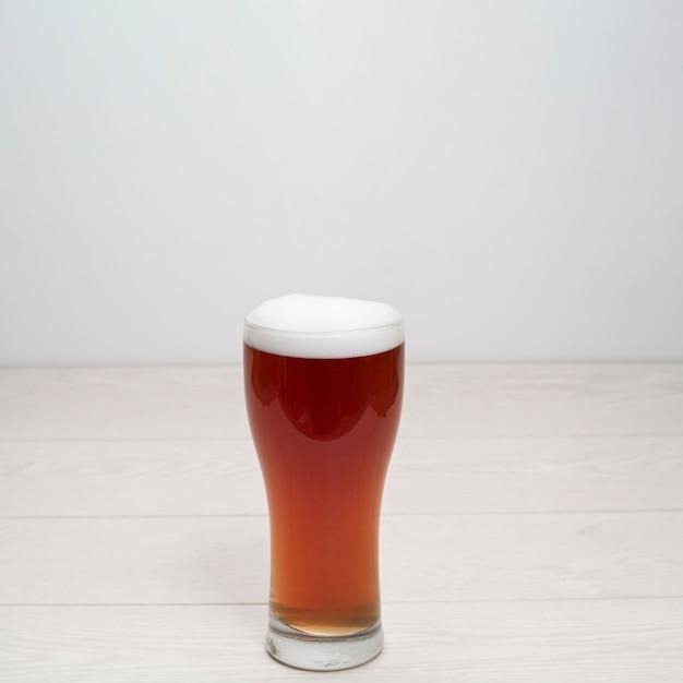 Bierglas met schuim op tafel Gratis Foto
