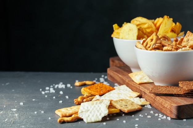 Biersnacks op stenen tafel. verschillende crackers, chips. bovenaanzicht Premium Foto