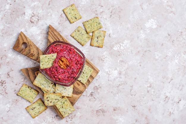 Bietenhummus op snijplank met zoute koekjes op lichte oppervlakte Gratis Foto