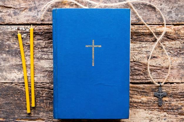 Bijbel, kruis en kaarsen voor huisgebed op een houten achtergrond Premium Foto