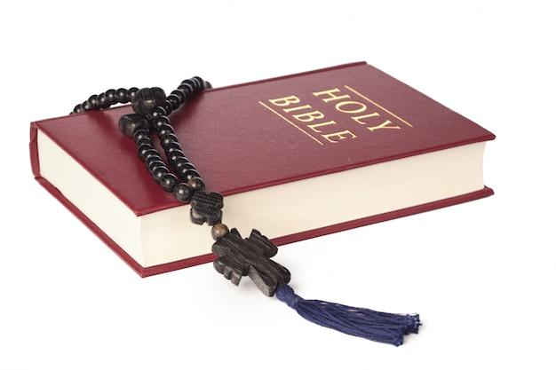 Bijbel op een witte achtergrond. heilig boek en houten rozenkrans. Premium Foto