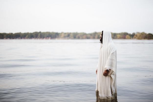 Bijbels tafereel - van jezus christus die in het water staat met een onscherpe achtergrond Gratis Foto