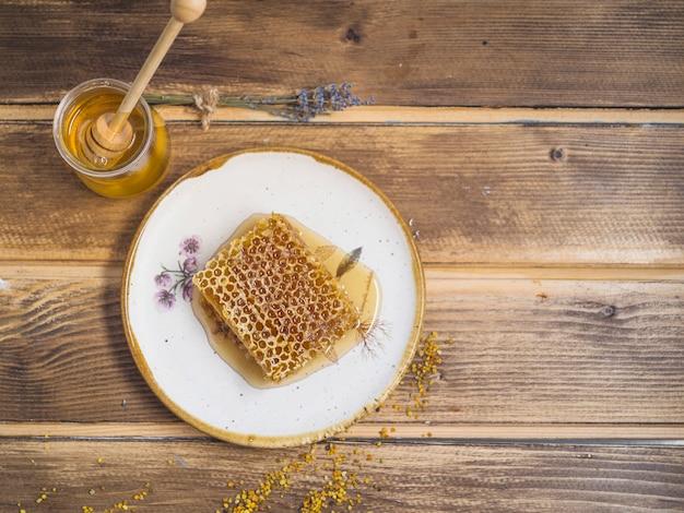 Bijenpollen; honingpot en honingraat stuk op witte plaat over de tafel Gratis Foto