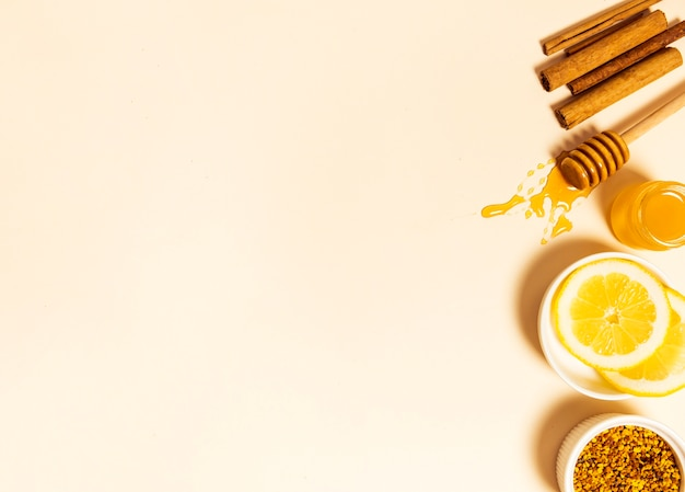 Bijenpollen; schijfje citroen; honing; honingdipper en kaneel gerangschikt in een rij op beige achtergrond Gratis Foto