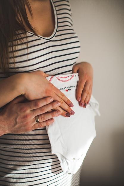 Bijgesneden afbeelding van een mooie zwangere vrouw en haar knappe man knuffelen de buik en houdt kleine kinderkleding. geluk. moeder en babythema. Premium Foto