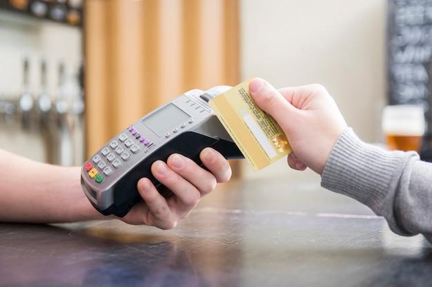Bijgesneden afbeelding van een persoon die met een creditcard betaalt Gratis Foto