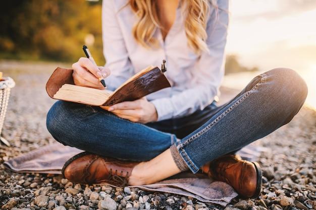 Bijgesneden afbeelding van gerichte modieuze mooie blanke vrouw zitten in de buurt van rivier en bedrijf notebook. Premium Foto
