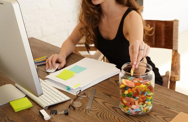 Bijgesneden afbeelding van jonge gestrest vrouw snoep eten op de werkplek op kantoor. het meisje pakt snoep uit een grote glazen pot met lollies die op een bureaublad staan. stress en junkfood concept Gratis Foto