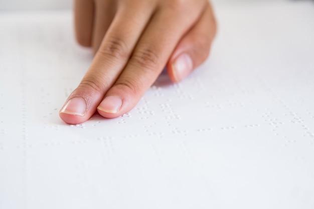 Bijgesneden afbeelding van kind hand braille boek lezen Premium Foto
