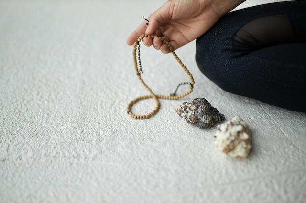Bijgesneden afbeelding van onherkenbare vrouw met mala-kralen voor gebed of meditatie om bij te houden tijdens het chanten of herhalen van mantra, zittend op de vloer. Gratis Foto