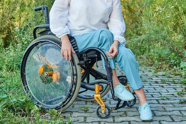 Bijgesneden afbeelding van vrouw in rolstoel wandelen in park buitenshuis, zonnig herfstweer. Premium Foto