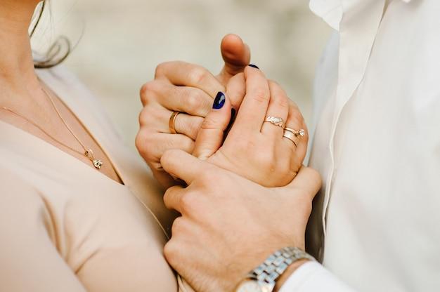 Bijgesneden foto jong getrouwd stel houdt handen met ringen, man en vrouw buitenshuis. achter mening van paar dat zich op aard bevindt Premium Foto