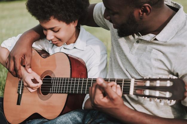 Bijgesneden foto van afro dad tonen lessen om te spelen Premium Foto