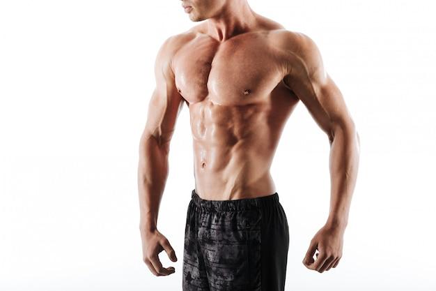 Bijgesneden foto van bezwete atletische man in zwarte korte broek rust na de training Gratis Foto