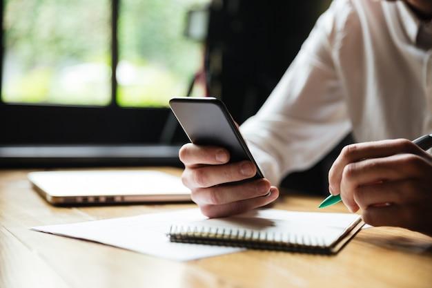 Bijgesneden foto van jonge man in wit overhemd met smartphone, terwijl rust na papierwerk Gratis Foto