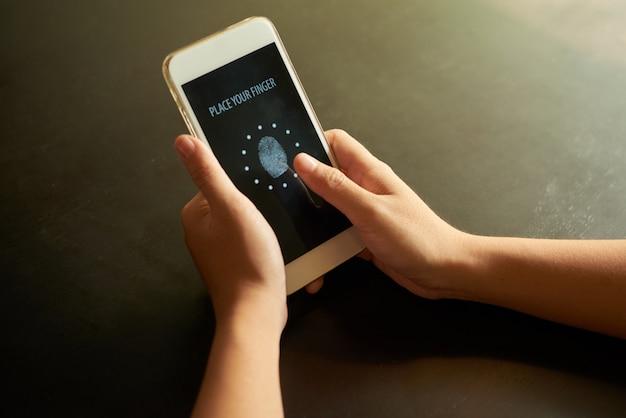 Bijgesneden handen die vinger op de identificatievlek op touchscreen plaatsen Gratis Foto