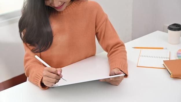 Bijgesneden opname jonge vrouw met pen op digitale tablet. Premium Foto