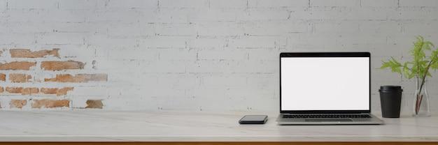Bijgesneden opname van moderne werkruimte met leeg scherm laptop, smartphone, decoratie en kopie ruimte op marmeren bureau Premium Foto