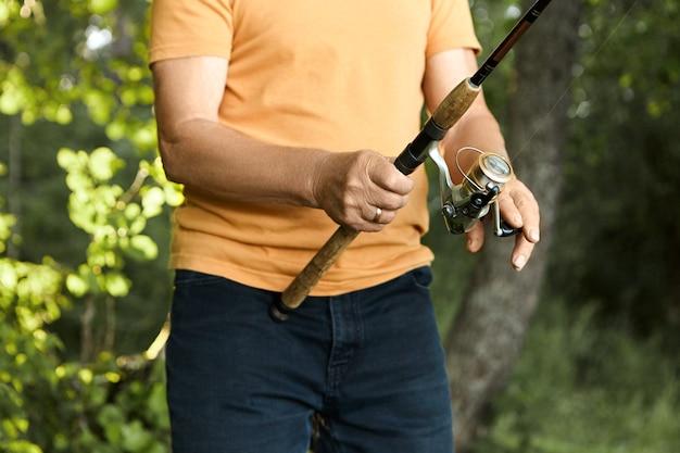 Bijgesneden portret van onherkenbare oudere visser die een oranje t-shirt en een zwarte spijkerbroek draagt met visgerei terwijl hij buiten aan het vissen is in de wilde natuur. visserij, activiteit en hobbyhobby Gratis Foto